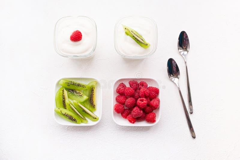 Naturligt yoghurt med färska hallon och kiwi arkivbilder