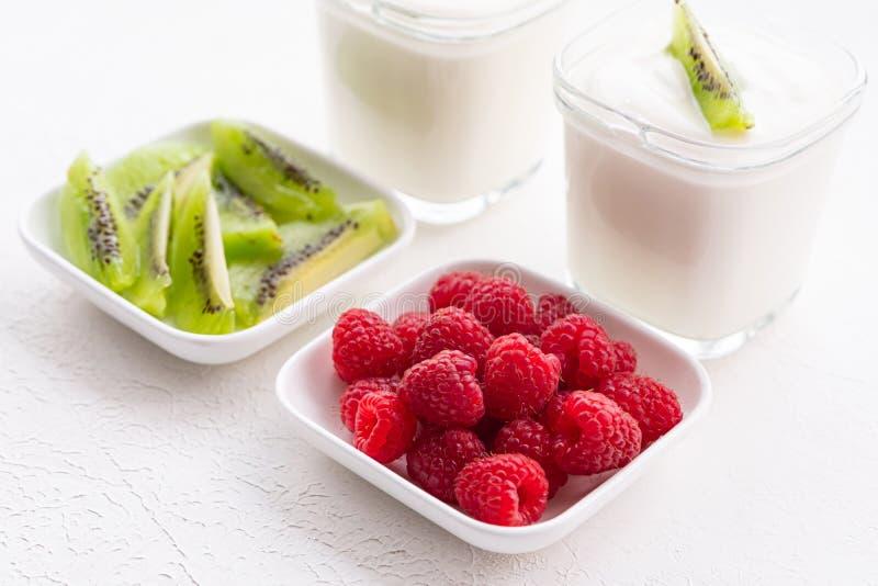 Naturligt yoghurt med färska hallon och kiwi arkivbild