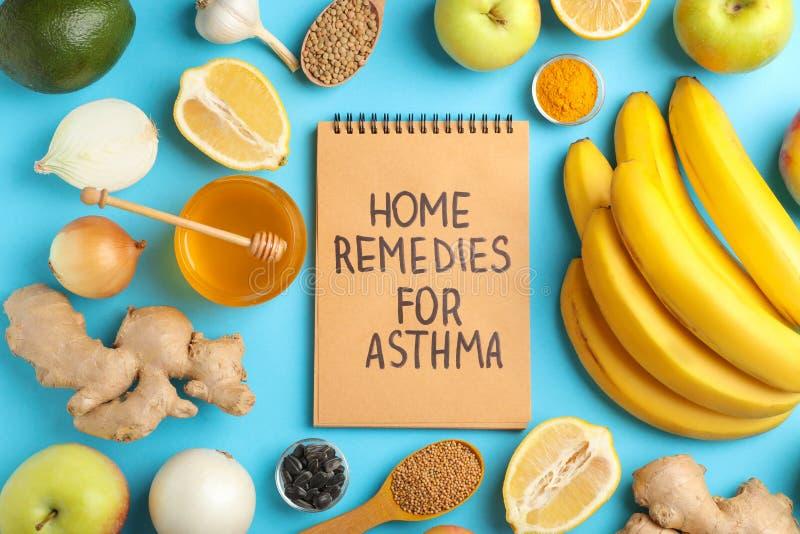 Naturprodukter och anteckningsbok med textHEMBOTER FÖR ASTMA på färgbakgrund royaltyfri foto