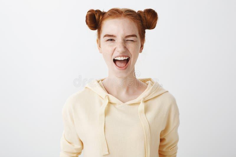 Naturschönheit und Leutekonzept Porträt der erstaunlichen emotionalen Frau mit dem roten Haar und zwei Brötchen, Zunge zeigend un lizenzfreie stockfotografie