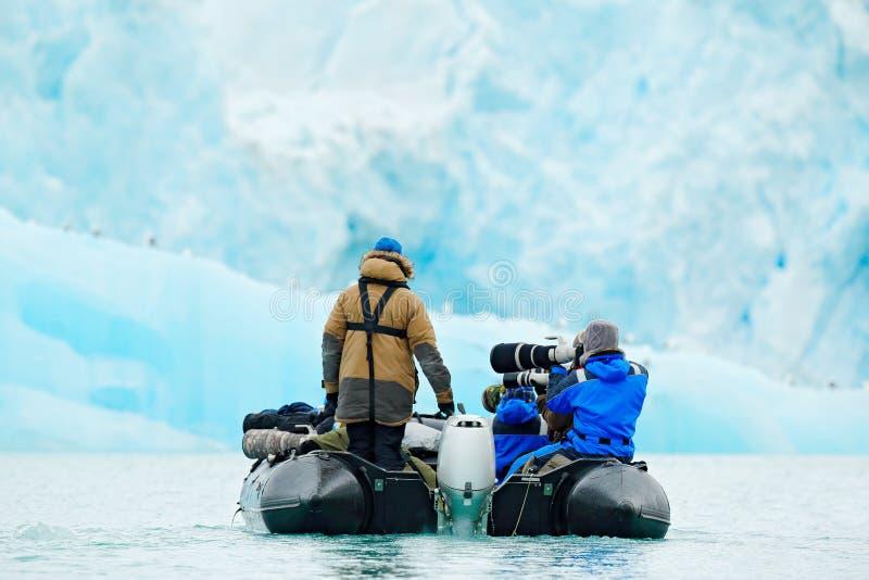 Naturvänner i arktiska Svalbard, Norge Motoriskt fartyg med turister på ishavet, snöig berg i bakgrund Arktisk kryssning in arkivfoto