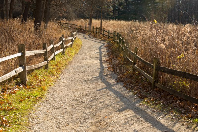 Naturweg mit splitrail Zaun in der kleinen roten Schulhaus-Natur-Mitte stockbild
