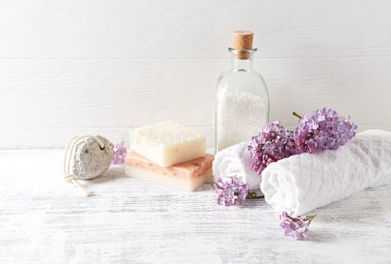 Natuurlijk badzout, zeep, katoenen handdoeken en lilac bloemen symbolisch beeld stock fotografie