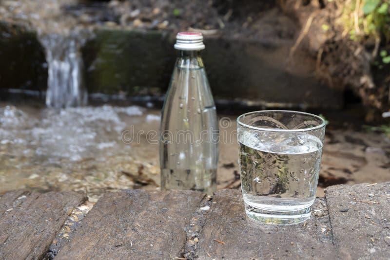 Natuurlijk ecologisch bronwater Glasfles en glas van koud watertribunes in aard royalty-vrije stock foto