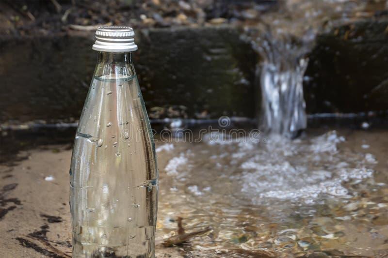 Natuurlijk ecologisch bronwater Glasfles met koud watertribunes in aard royalty-vrije stock fotografie