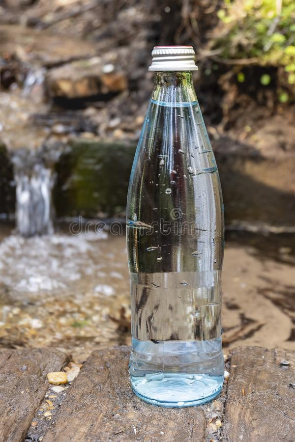 Natuurlijk ecologisch bronwater Glasfles met koude bronwatertribunes in aard royalty-vrije stock afbeeldingen