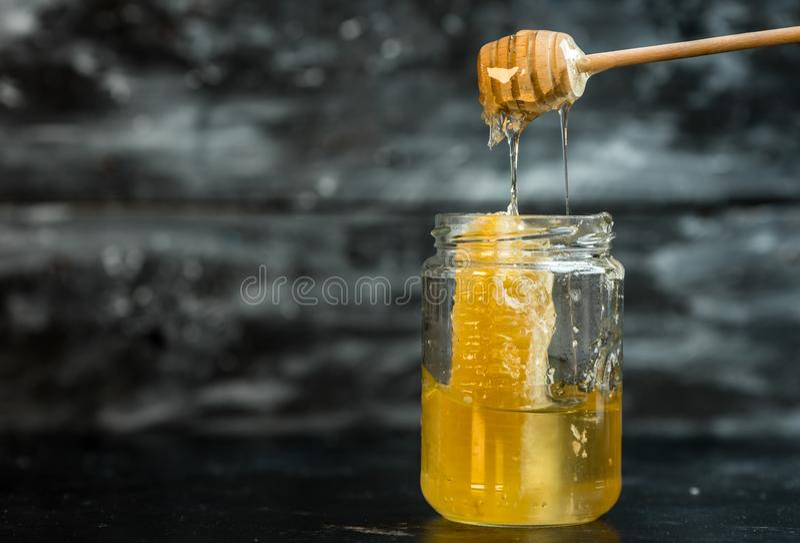 Natuurlijk, gezond ingrediënt - een kruik gouden honing op een donkere achtergrond royalty-vrije stock afbeeldingen