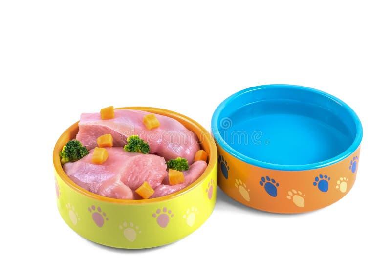Natuurlijk hondevoer en water in ceramische die kommen op wit worden geïsoleerd royalty-vrije stock afbeeldingen