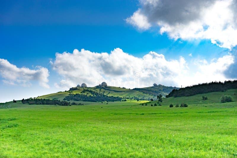 Natuurlijk landschap met een groen die gebied met gras onder de blauwe hemel met wolken wordt behandeld royalty-vrije stock foto's
