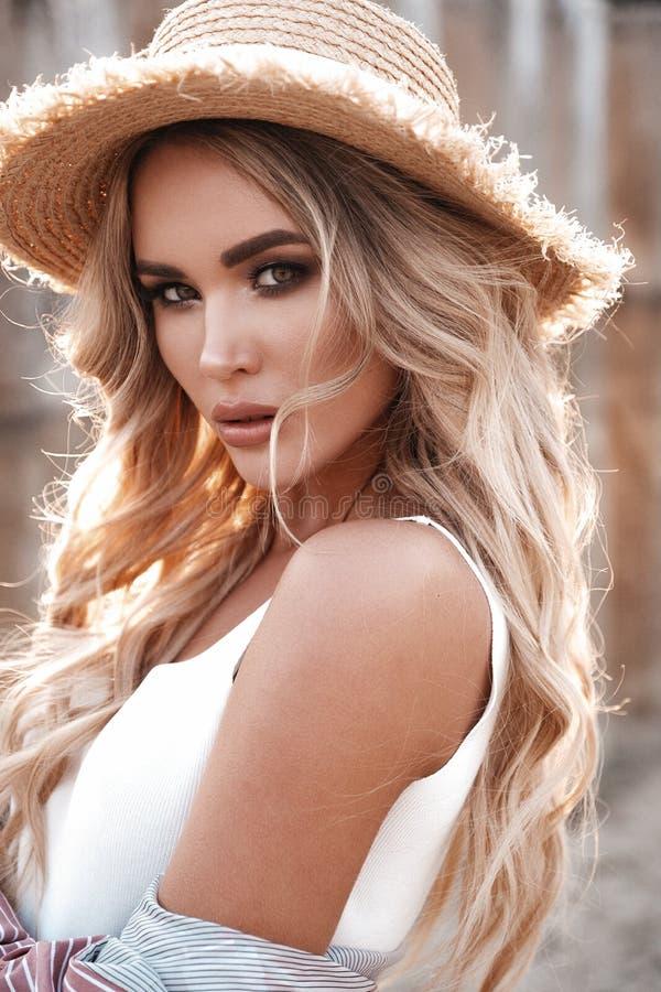 Natuurlijk levensstijlportret van een mooie aantrekkelijke jonge vrouw met lang los blondehaar in een strohoed Apple-de lentetuin royalty-vrije stock afbeeldingen