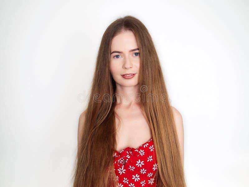 Natuurlijk licht portret van jonge mooie blonde vrouw met lang haar in het uitstekende rode kleding glimlachen die camera over wi stock afbeelding