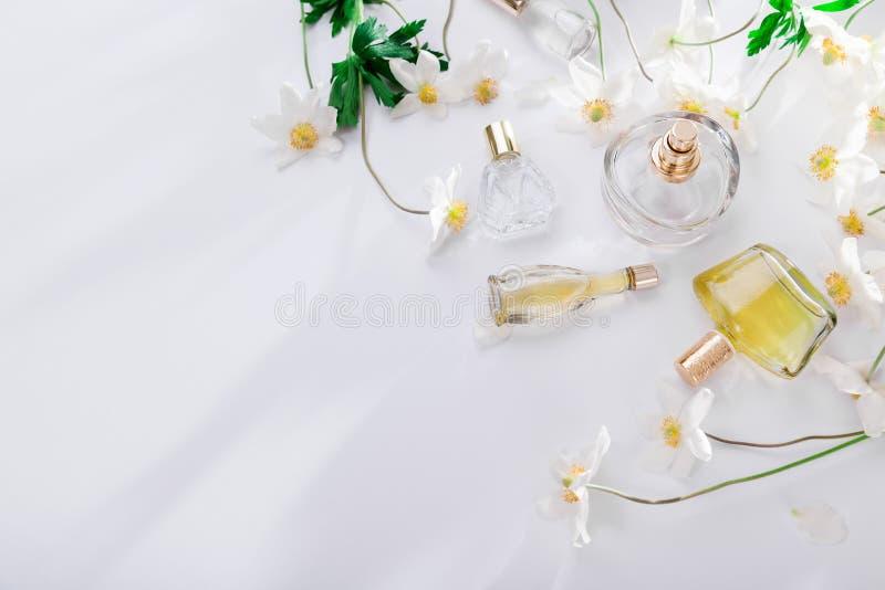 Natuurlijk parfumconcept Flessen parfum met witte bloemen Bloemengeur stock afbeelding