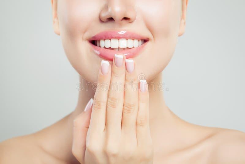 Natuurlijk schoonheidsconcept Close-up vrouwelijke glimlach met natuurlijke roze lippen en Franse manicurehand stock foto's