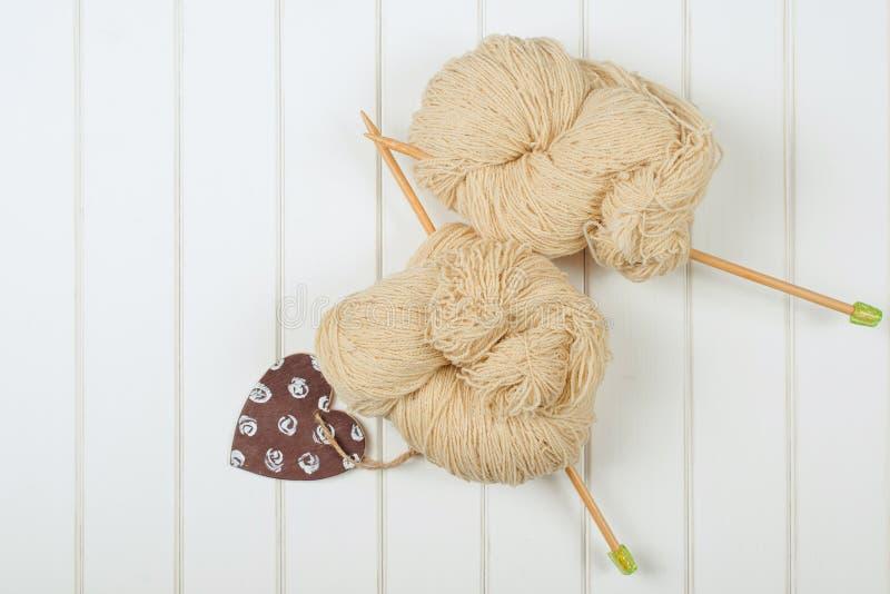 Natuurlijk wollen garen met houten naalden op witte houten achtergrond royalty-vrije stock foto