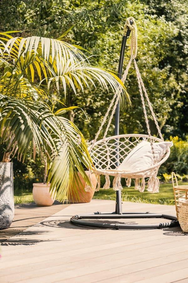 Natuurlijk zonnig terras met een koordhangmat die van een metaal hangen royalty-vrije stock fotografie