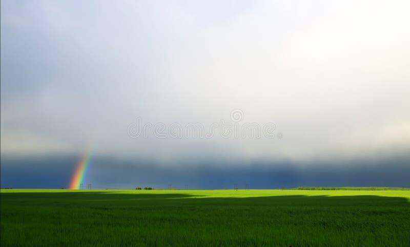 natuurlijke achtergrond met heldere kleurrijke regenboog in distan royalty-vrije stock afbeelding
