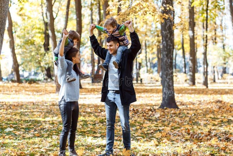 Natuurlijke beelden van een gelukkige familie van vier die pret outsiade op een zonnige de herfstdag hebben Samenhorigheid en gel stock foto's
