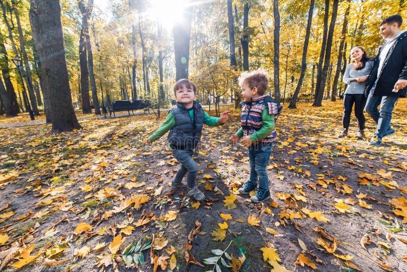 Natuurlijke beelden van een gelukkige familie van vier die pret outsiade op een zonnige de herfstdag hebben Samenhorigheid en gel royalty-vrije stock afbeeldingen