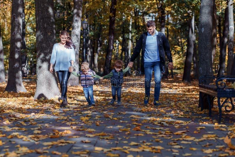 Natuurlijke beelden van een gelukkige familie van vier die pret outsiade op een zonnige de herfstdag hebben Samenhorigheid en gel royalty-vrije stock foto's