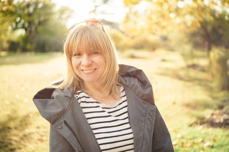 Natuurlijke blonde gelukkige vrouw die zich in een herfstpark bevinden De herfst, openlucht en levensstijlconcept stock foto