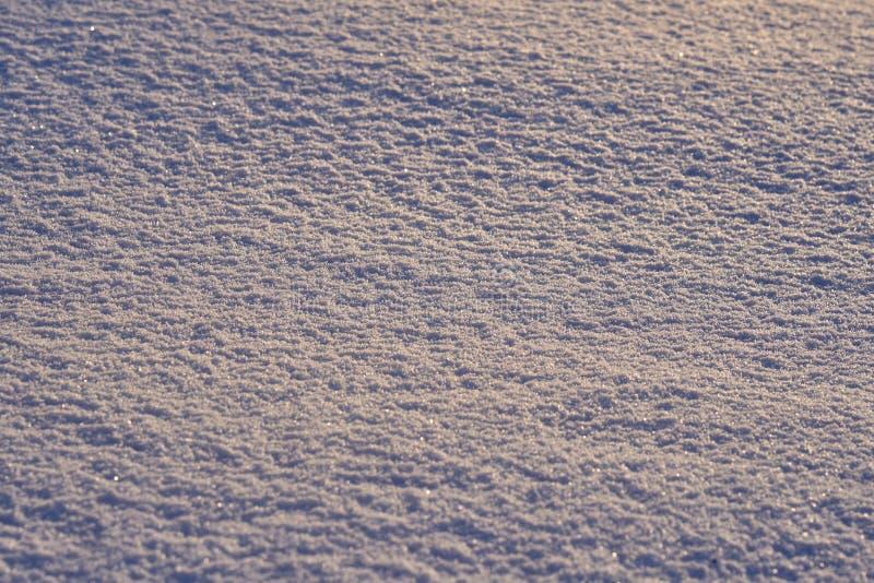 Natuurlijke die achtergrond - ijsoppervlakte van sneeuw door de stralen van de avondzon wordt verlicht stock afbeelding
