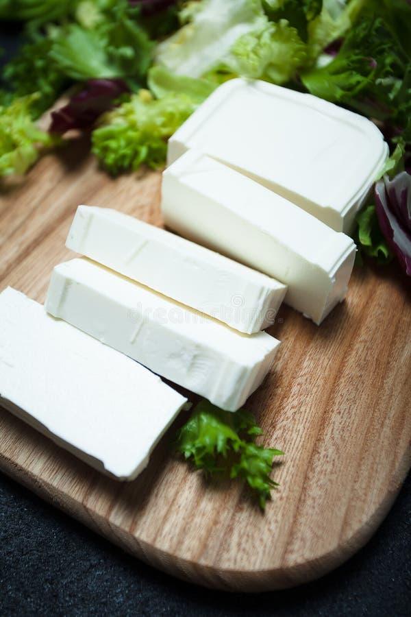 Natuurlijke die feta-kaas van koemelk met plakken wordt gesneden stock afbeelding