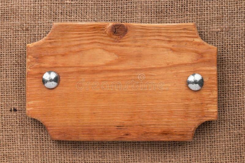Natuurlijke die textuur van het kader van raad met bouten wordt gemaakt, liggend op de jute stock afbeelding