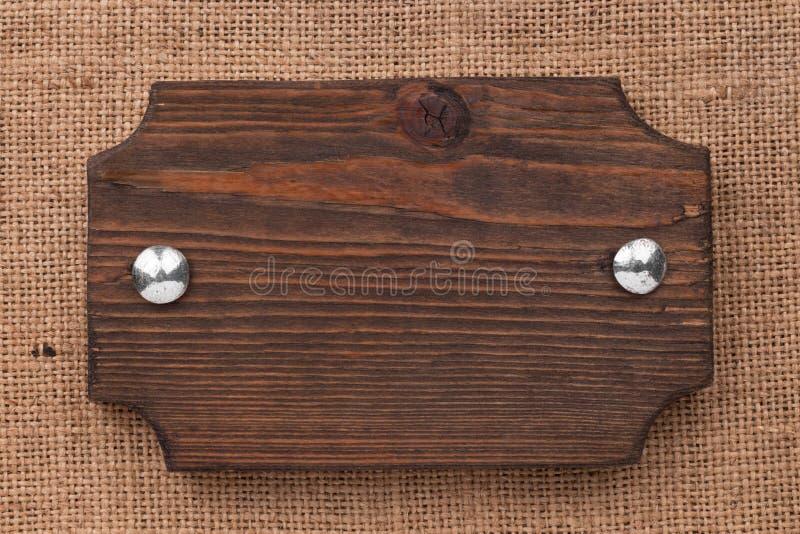 Natuurlijke die textuur van het kader van raad met bouten wordt gemaakt, liggend op de jute stock foto's