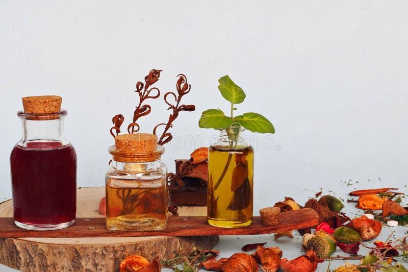 Natuurlijke geneeskunde: Selectie van 3 flessen met etherische oliën Plantenteelt in een pot stock afbeeldingen