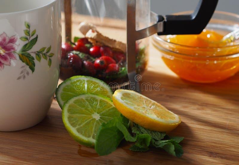 Natuurlijke griepbehandeling: stilleven met kalk, citroen, muntblad, oranje jam, en bessenthee stock foto's