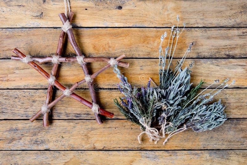 Natuurlijke Heks - rustieke tak pentagram en droge kruiden stock foto