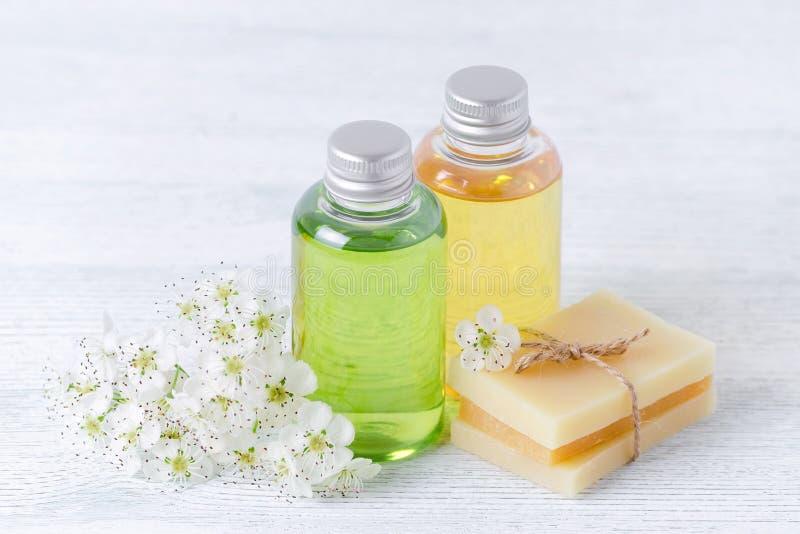 Natuurlijke kosmetische flessen en met de hand gemaakte zeepbar met verse bloemen op grijze achtergrond stock afbeelding