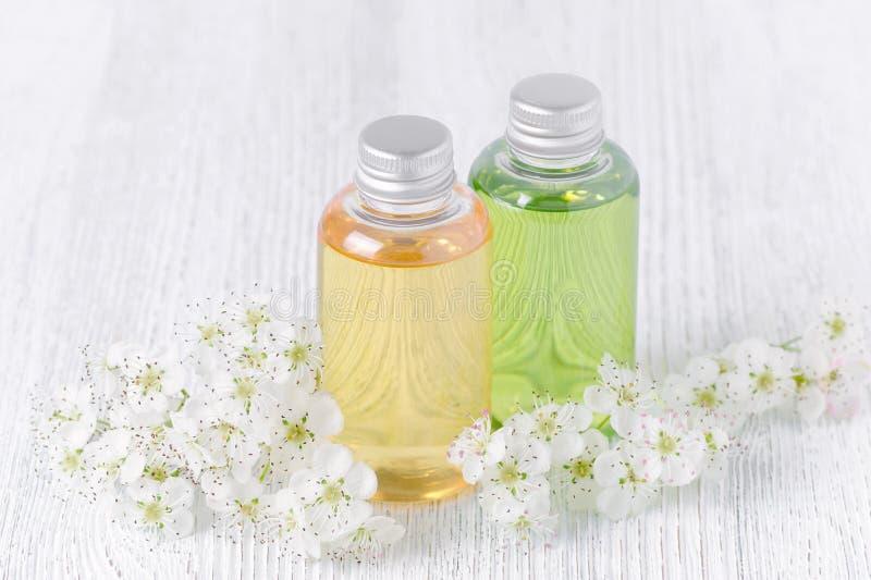 Natuurlijke kosmetische flessen met verse bloemen op grijze achtergrond stock foto