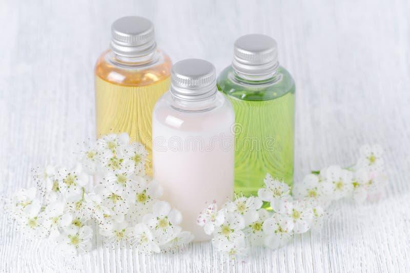 Natuurlijke kosmetische flessen met verse bloemen, wit, groen en geel stock foto's