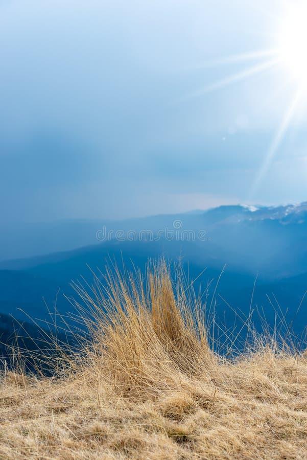 Natuurlijke landschapsmening van bergen, gras en sterke zonstralen, mooie achtergrond voor ontwerpen en kaarten Vroeg de lentelan royalty-vrije stock afbeelding