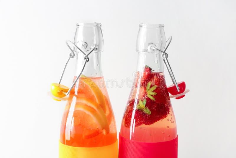 Natuurlijke limonade met aardbei in glasflessen op witte achtergrond royalty-vrije stock foto's