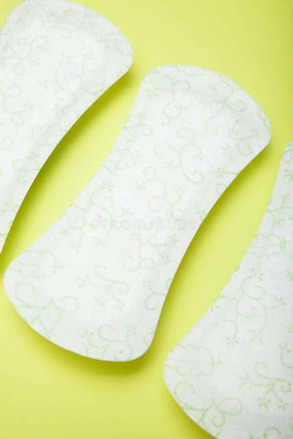 Natuurlijke maandverbanden, handdoek, stootkussen, menstrueel die stootkussen op groene achtergrond wordt geïsoleerd menstruatie stock foto