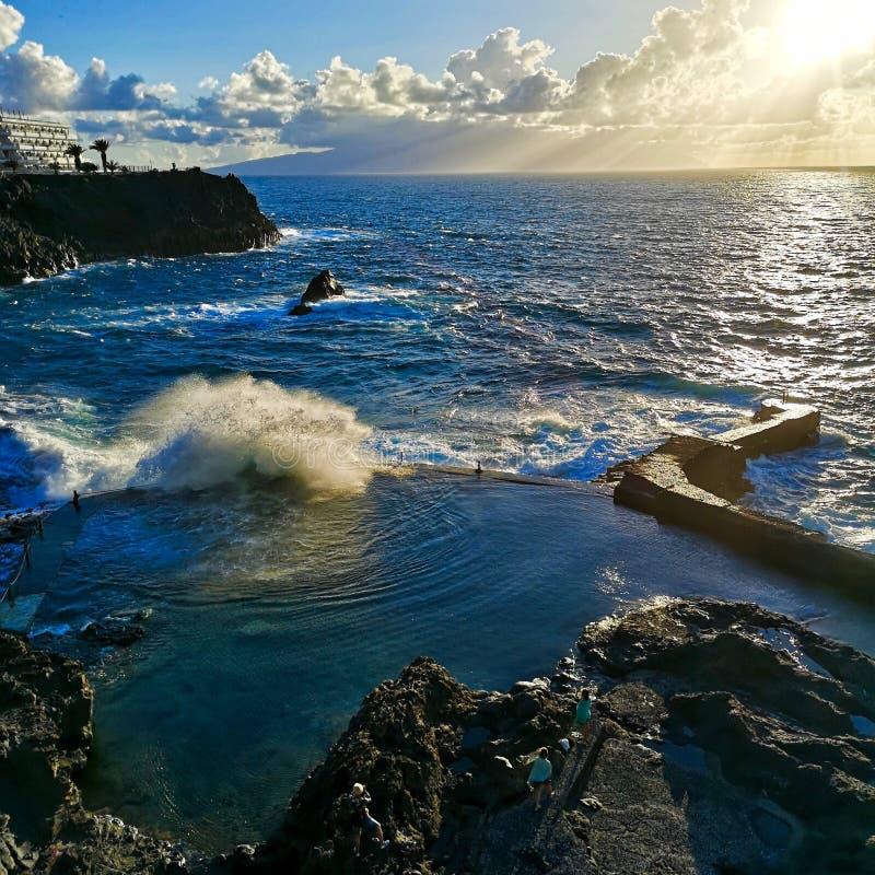 Natuurlijke pool en golven die terwijl de zon in Los Gigantes, Tenerife, Spanje plaatst bespatten stock foto