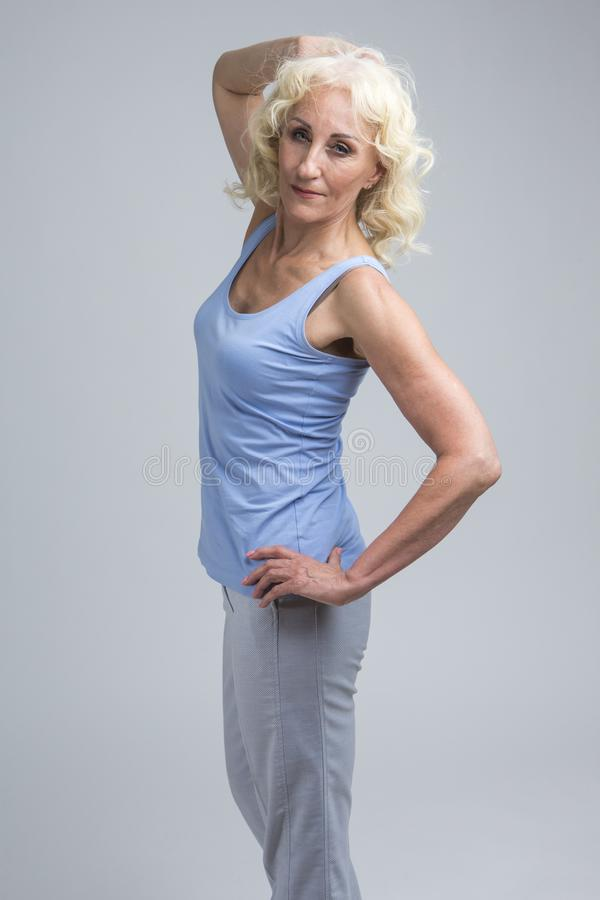 Natuurlijke portret van de Alluring Mature Blond Woman in Blue Tank Top Posing Against White Background in Studio stock foto