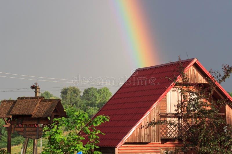 Natuurlijke regenboog over het dak van het huis royalty-vrije stock fotografie