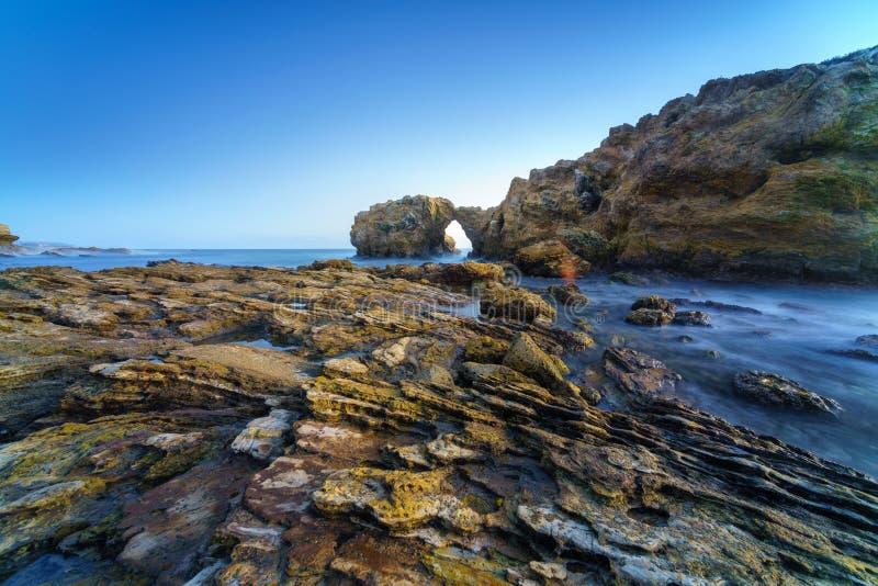 Natuurlijke rotsboog, klip en strand stock foto