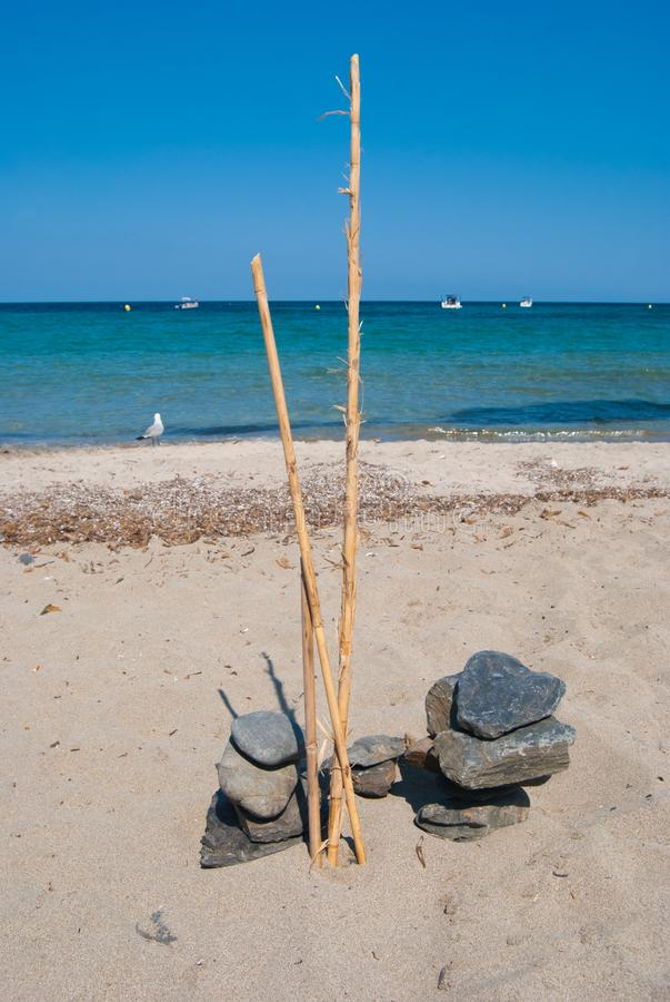 Natuurlijke samenstelling van overlappend kiezelstenen en bamboeriet op een zandig strand stock afbeelding
