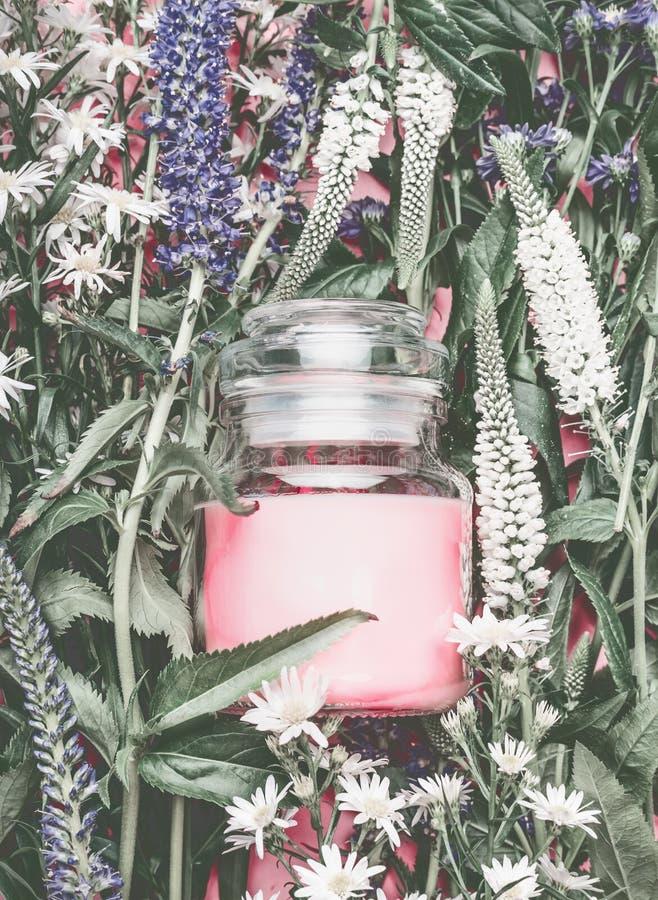 Natuurlijke schoonheidsmiddelenkruik met pastelkleur roze room op kruidenbladeren en wilde bloemen, leeg etiket voor het brandmer stock afbeeldingen