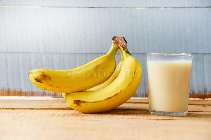 Natuurlijke voeding met banaanfruit en melk in glas op houten stock fotografie