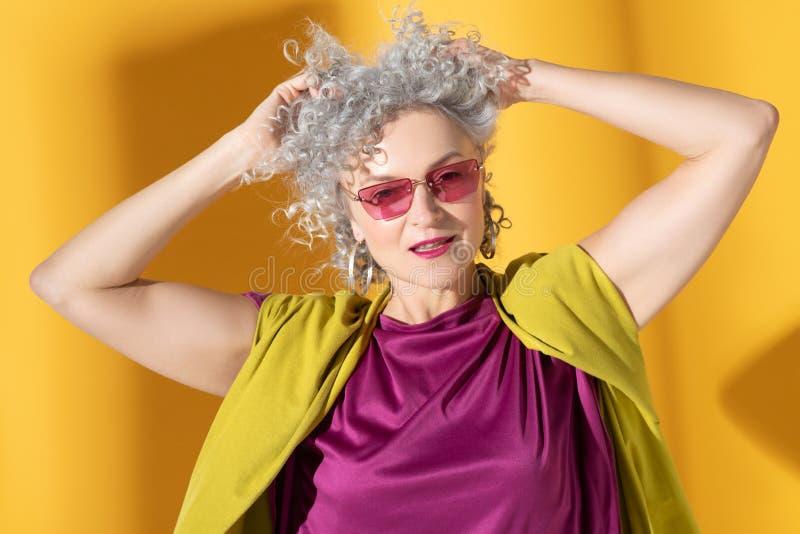 Natuurlijke vrouw met roze lippen die haar krullende haar aanraken royalty-vrije stock afbeelding