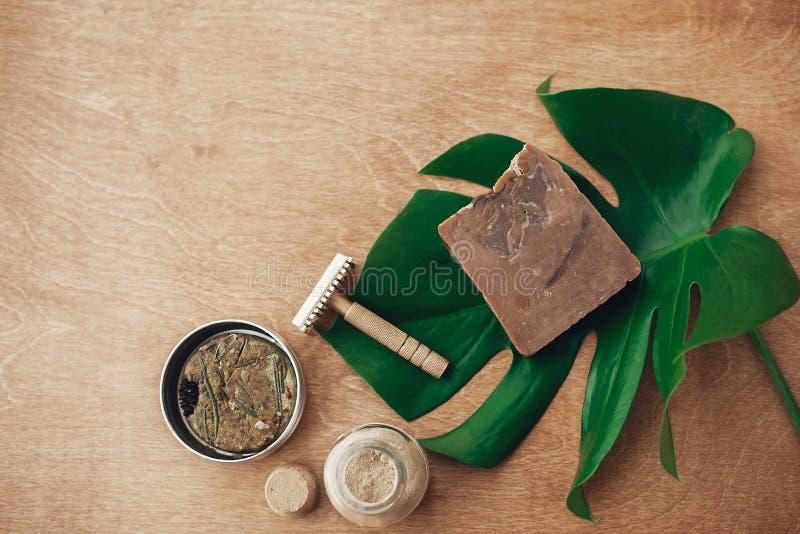 Natuurlijke zeep, stevige shampoo in metaaltin, opnieuw te gebruiken scheermes, ubtan op houten achtergrond met groen monsterabla royalty-vrije stock foto's