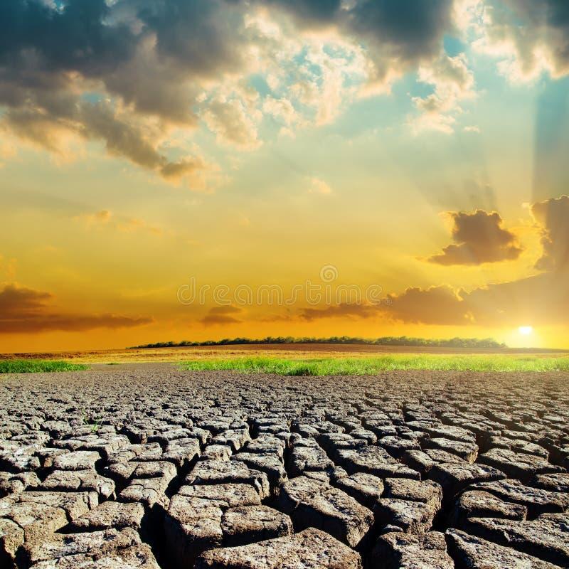 Natuurramp met droogteaarde en zonsondergang stock afbeelding