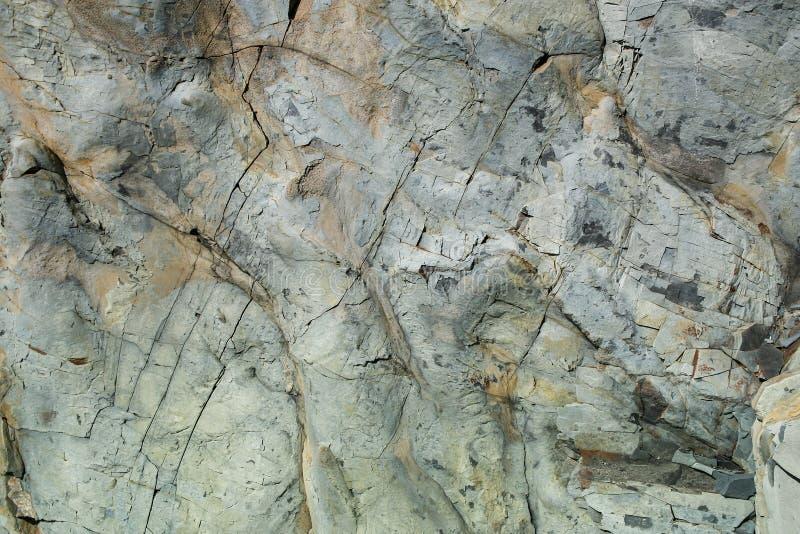 Natuursteen grunge grijs-bruine ongelijke muur met barsten royalty-vrije stock foto's