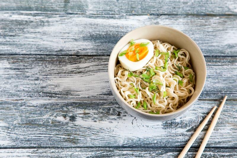 Natychmiastowi kluski na drewnianym tle Gotujący chińscy natychmiastowi kluski Zupni Ramen z jajkiem i rzodkwią obraz stock
