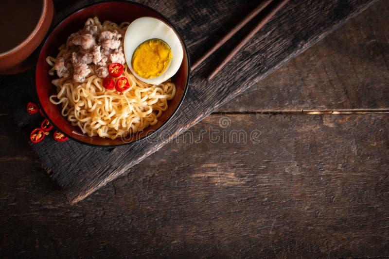 Natychmiastowy kluski z wieprzowin?, jajko i warzywa na czarnym pucharze na drewno stole tam, jeste?my chili, chopstick i pi? szk zdjęcia royalty free